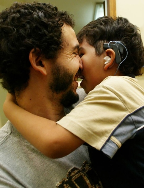A young boy is held by his father as he hears for the first time